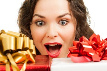 beautifully wrapped: Beautiful young surprised woman looking at beautifully wrapped Christmas gifts