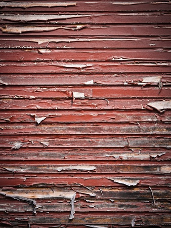 worn structure: A grungy old wall with red paint flaking off Stock Photo