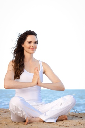Beautiful healthy & fit young woman meditating on the beach