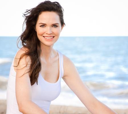 ni�as sonriendo: Retrato de una bella mujer joven y sana sentado en la playa Foto de archivo