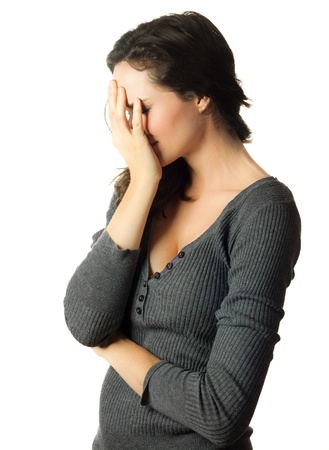 A very sad and depressed woman hiding her face in her hands