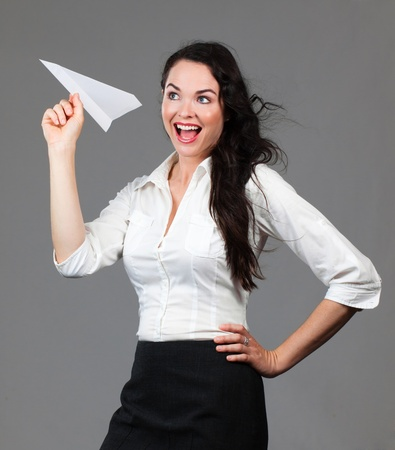 Beautiful young business woman holding a paper airplane smiling photo