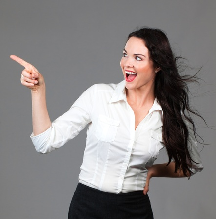 Beautiful young smiling business woman pointing to copyspace photo