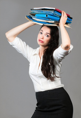 Portrait of a tired and overworked business woman carrying paperwork on her head photo
