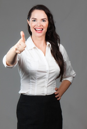 Portrait of successful happy business woman giving thumbs up photo