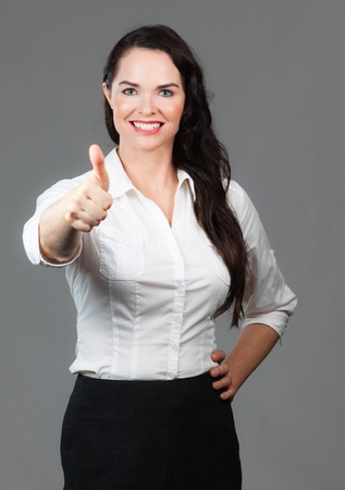 Portrait of successful beautiful business woman giving thumbs up photo