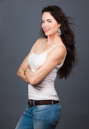 A portrait of a young beautiful woman wearing jeans and singlet photo