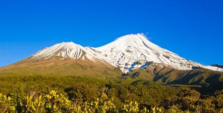 egmont: Mt Egmont or Mt Taranaki, New Zealand, covered in snow, against a beautiful blue sky