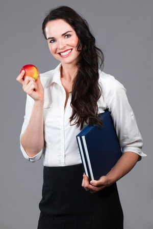 Portrait of a confident attractive business woman holding book and an apple photo