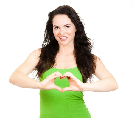 Beautiful smiling young woman symboling a love heart with hands  Isolated over white  photo
