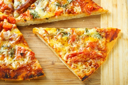 pizza base: A slize of delicious homemade pizza on a wooden chopping board