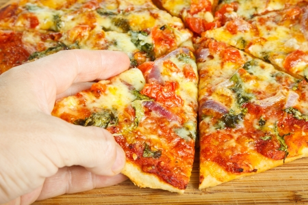 Close-up of a hand taking a slize of homemade pizza Stock Photo - 13884660