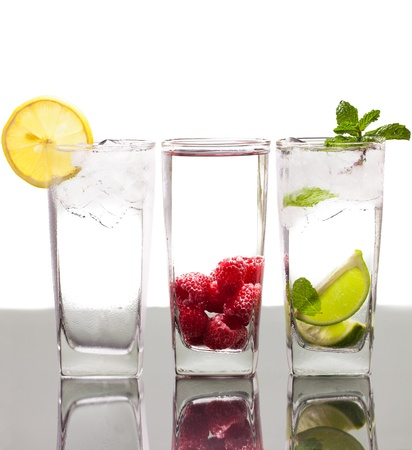 Three colorful alcoholic drinks with berries, fruit and ice  On a table with reflection and isolated over white  photo