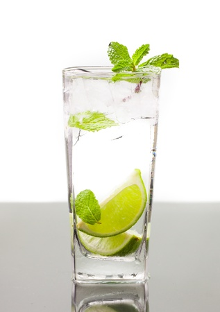 A cold alcoholic drink, mojito, with lime, mint soda and ice  On table with refelction and isolated over white Stock Photo - 13892478
