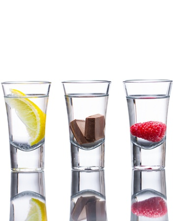 Three vodka shots flavoured with raspberry, lemon, and chocolate. Reflection in table and isolated on white.