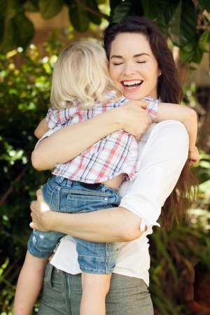 A beautiful young happy loving mother smiling and hugging her young child. photo