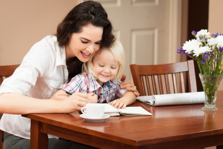 A happy mother and son sitting at table writing and drawing Stock Photo