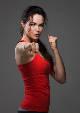 An attractive sexy woman throwing a punch during boxing exercise Stock Photo