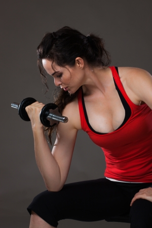 A beautiful young woman sitting down lifting weights photo