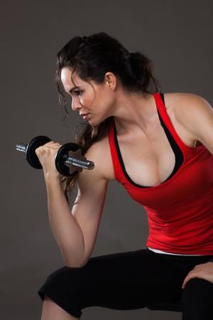 lifting weights: Una joven y bella mujer sentada levantamiento de pesas