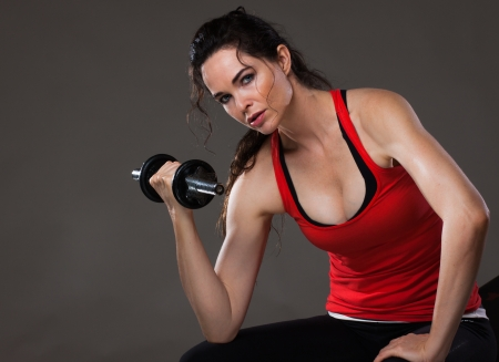 A beautiful young woman sitting down lifting weights and looking at camera photo