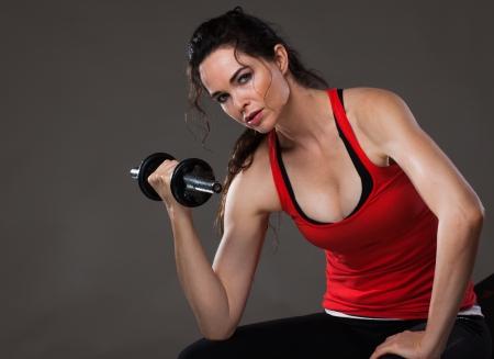 A beautiful young woman sitting down lifting weights and looking at camera photo
