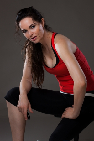 A young beautiful woman sitting down and having a rest after exercise  photo