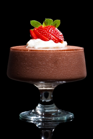 sweet treats: Chocolate mousse dessert with strawberries and cream. Isolated on black. Stock Photo