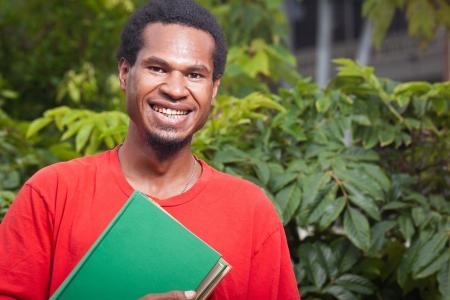 Nuova Guinea: Ritratto di un felice sorridente giovane studente maschio da Sud-Est asiatico che porta i libri di scuola Archivio Fotografico