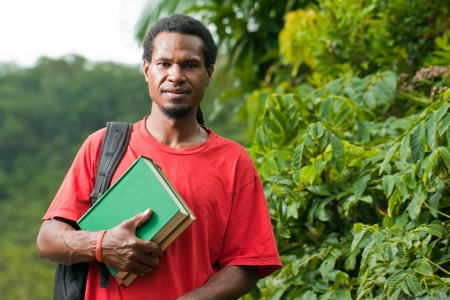 guinea: Young south east asian male student carrying books and backpack