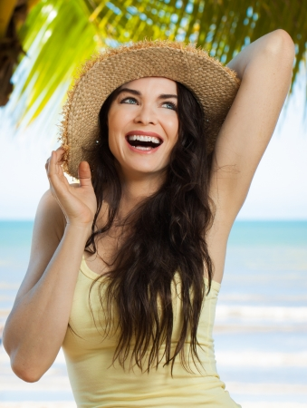 A happy young beautiful woman laughing and holding hat on a tropical beach with palm trees. photo