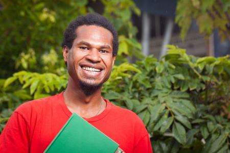 papua: A happy dark skinned malel student
