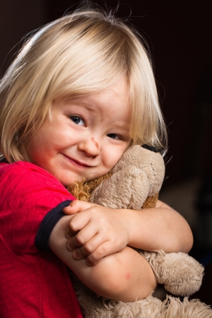 A cute injured little boy hugs his stuffed toy  photo