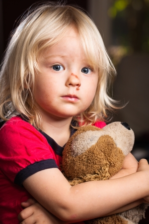 child patient: A sad cute injured boy holding a stuffed toy dog