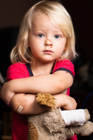 An injured cute little boy with band aid on his elbow, holding a puppy   Stock Photo