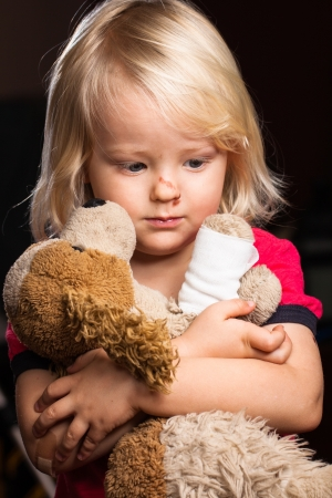stuffed animals: A cute injured little boy looking sad holding his stuffed dog toy   Stock Photo