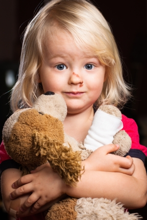 A injured cute little boy hugging his stuffed toy dog   photo