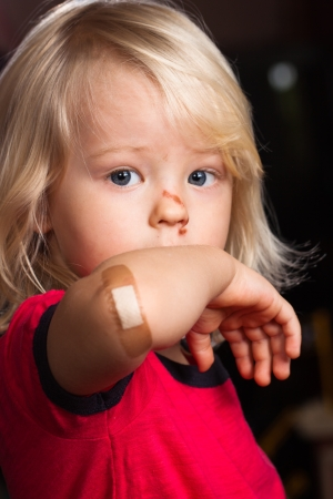 A young injured boy showing his elbow with  band aid on  photo