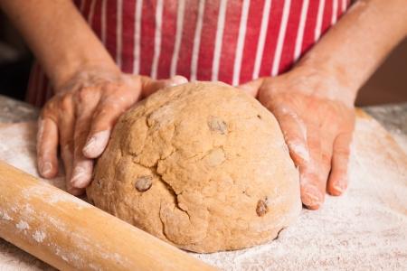 haciendo pan: Close-up de las manos amasando una masa de pan con pasas de una harina espolvoreada tabla de cortar