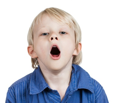 A tired cute young boy yawning. Isolated on white. Stock Photo - 15635918