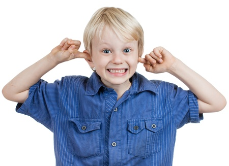A cute young boy smiling and sticking his fingers in his ears. Isolated over white. Stock Photo