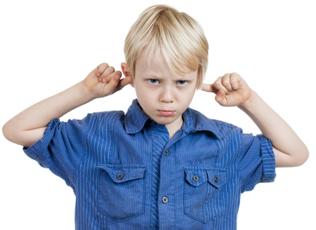 A grumpy cute young boy covers his ears with his fingers  Isolated on white  photo