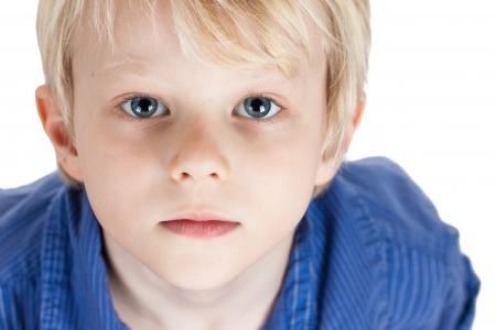 niños tristes: Un retrato de primer plano de un muchacho lindo serio joven aislado en blanco