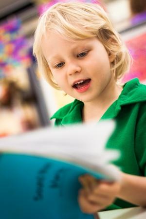 sachant lire et �crire: Un mignon petit gar�on heureux jeune �cole lisant un livre dans une salle de classe Banque d'images