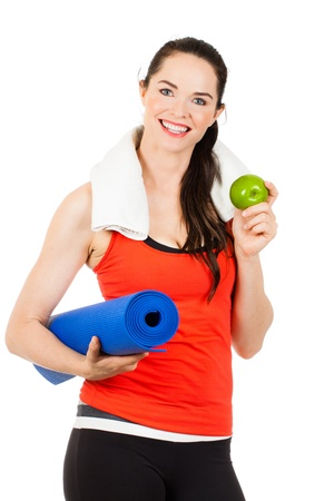 melle: A fit, healthy happy beautiful woman holds an apple and yoga mat  Isolated on white