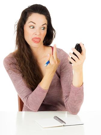 ACTITUD: Una mujer enojada est� dando a su tel�fono m�vil con el dedo aislado en blanco Foto de archivo