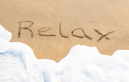 sand writing: Relax - written in the sand with a foamy wave underneath
