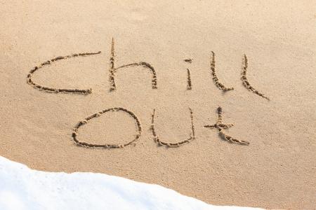 Chill out - escrito en la arena con una ola espumosa debajo