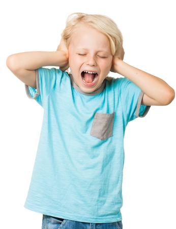 one eye closed: A young distressed young boy screams with his eyes shut and covers his ears with his hands  Isolated on white