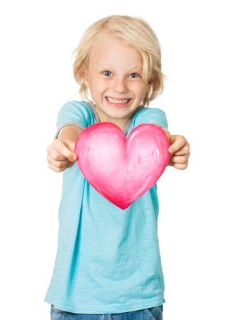 A very cute young blond boy smiling and holding out a love heart  Isolated on white  photo